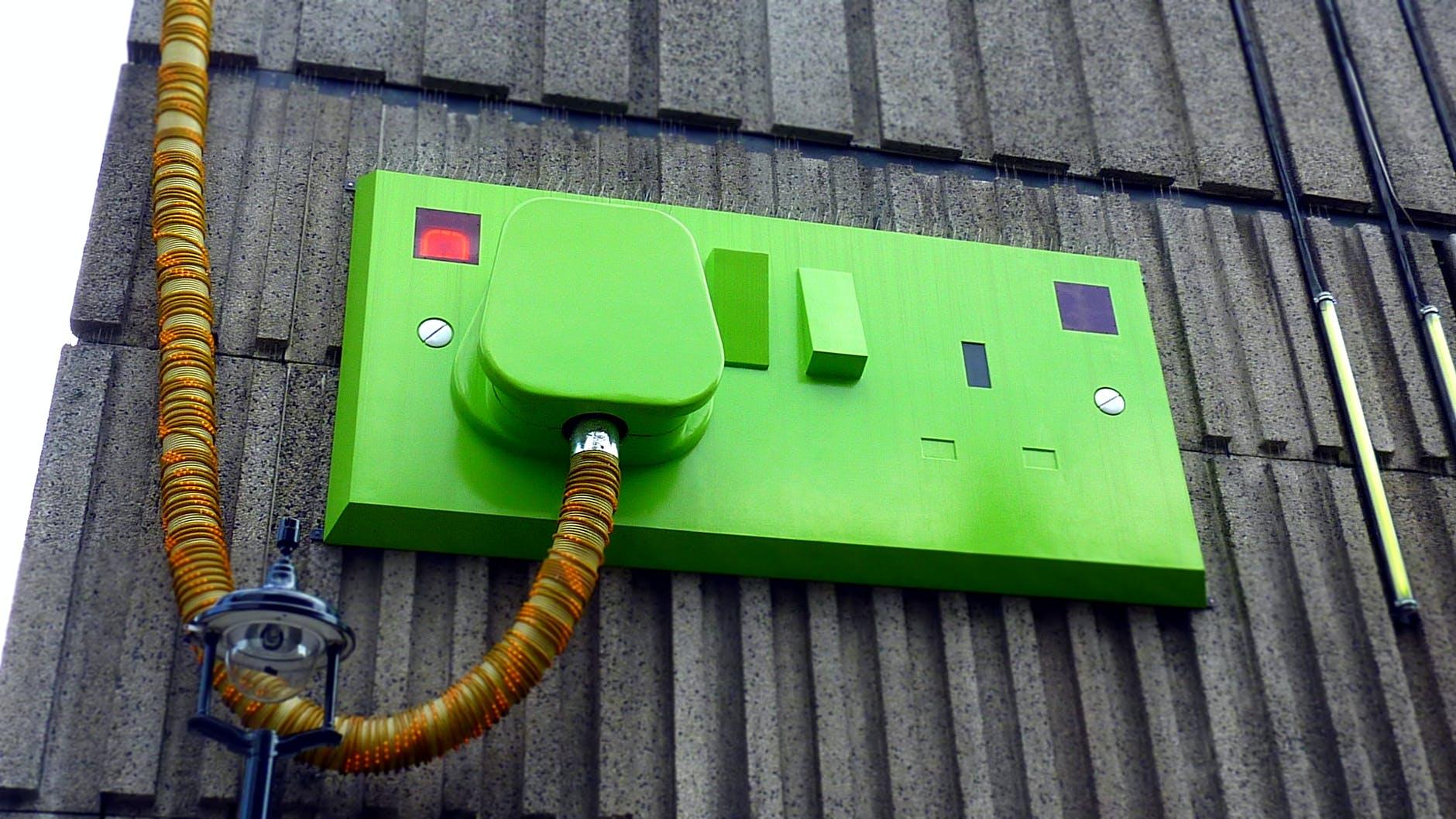 green rectangular corded machine on grey wall during daytime